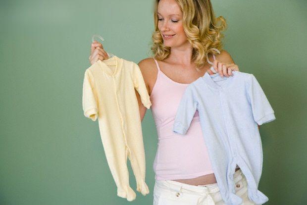 Pregnant woman choosing onesies